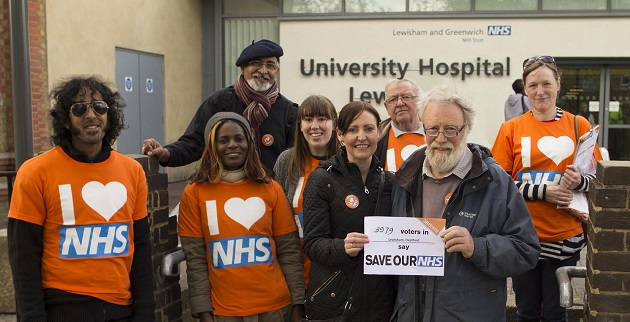 A group of people in 38 Degrees T shirts stand in front of the University Hospital of Lewisham. They're holding a sign saying, Save Our NHS.