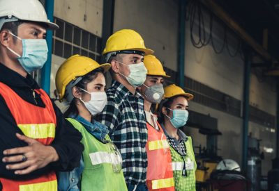 The image shows a line of workers wearing medical masks to protect themselves from coronavirus.