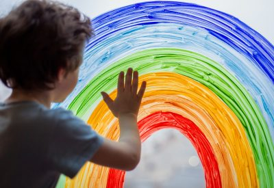 Image shows a child standing at a window, which has a rainbow painted on it.
