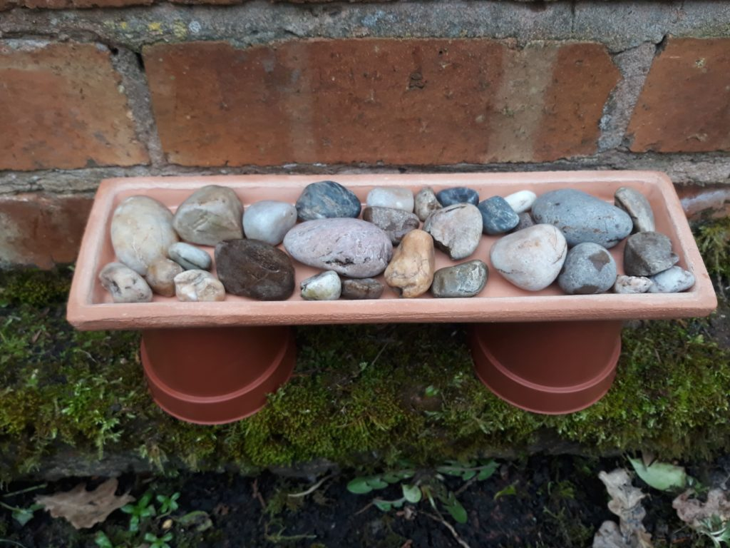 A shallow dish filled with clean stones is placed on top of two upturned plant pots
