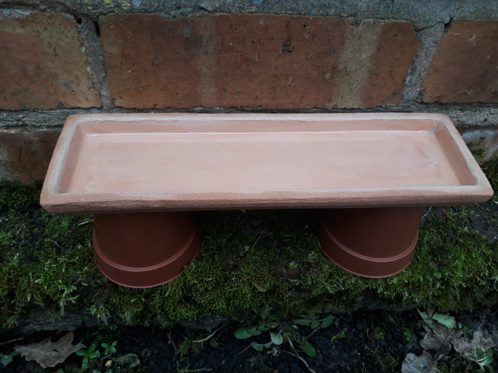 A shallow dish is placed on top of two upturned plant pots