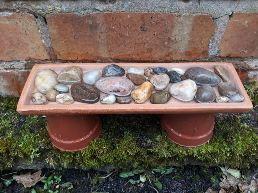 A shallow dish filled with clean stones is placed on top of two upturned plant pots. There is water in the dish.