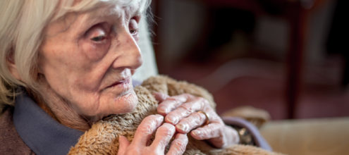 Photo of an older woman with white hair clutching a blanket towards her, with a despondent expression.